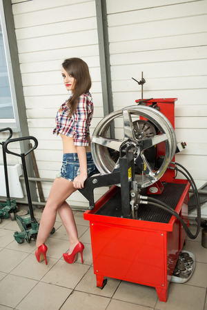 girl mechanic replace tires on wheels Stock Photo