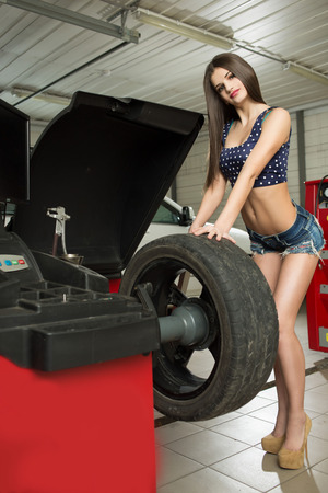replace: girl mechanic replace tires on wheels Stock Photo
