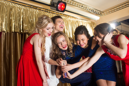 karaoke bar: happy girls singing into a microphone