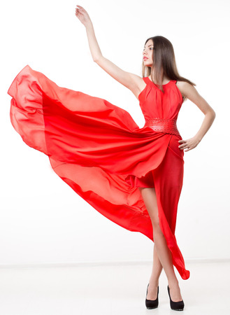 Young beauty woman in fluttering red dress.