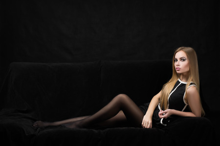 mature woman sexy: beautiful blond woman in a black dress on a dark background,