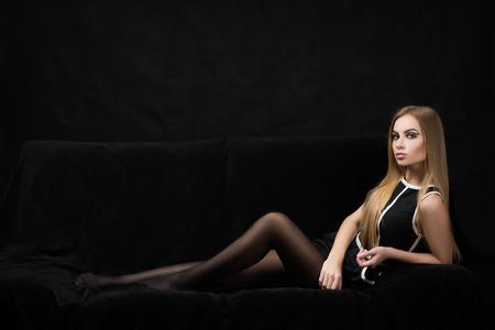 donne mature sexy: bella donna bionda in un abito nero su uno sfondo scuro,
