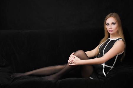 beautiful blond woman in a black dress on a dark background,