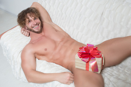 naked man: naked man on a couch with a gift