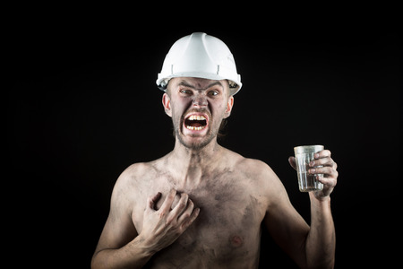 metallurgist: angry bearded working in a dirty helmet
