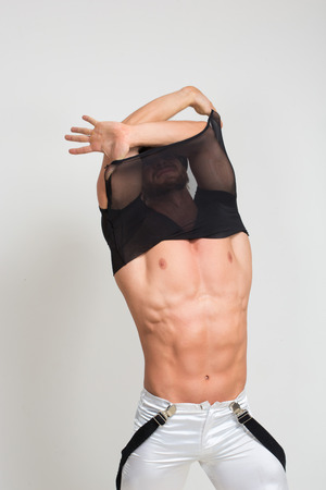 erotic male: Muscular sexy man taking off t shirt. Sexy stripper undressing. Stock Photo