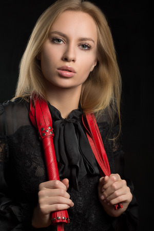spiked: beautiful woman in biting red whip Stock Photo