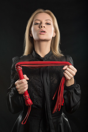 masochism: beautiful woman in biting red whip Stock Photo