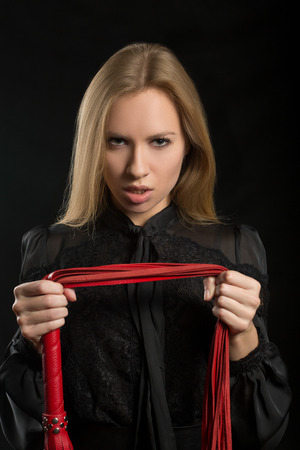 bondage girl: beautiful woman in biting red whip Stock Photo