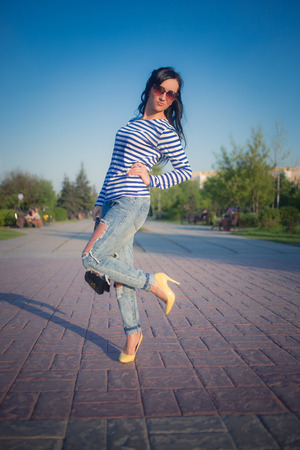 frock: beautiful brunette girl walks through the city streets. in torn jeans and frock