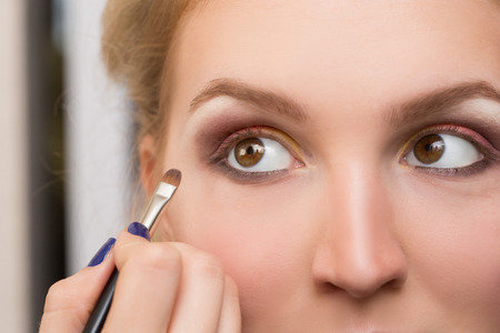 touch base: girl applied make-up on her eyes Stock Photo