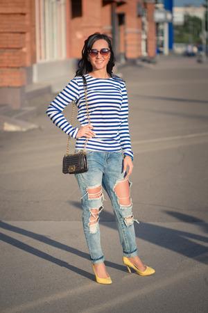 mooie brunette meisje loopt door de straten van de stad. in gescheurde spijkerbroek en jurk
