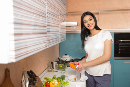 Smiling young woman in the kitchen with vegetables photo
