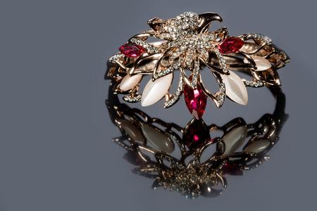 pietre preziose: golden bracelet with precious stones on grey background Archivio Fotografico