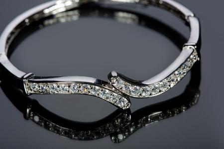 piedras preciosas: pulsera de oro con piedras preciosas sobre fondo gris