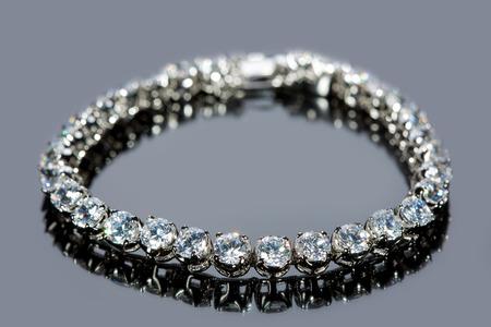 golden bracelet with precious stones on grey background photo