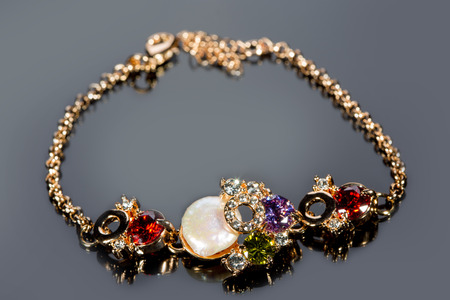 pietre preziose: golden bracelet with precious stones on grey background Archivio Fotografico