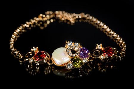 piedras preciosas: pulsera de oro con piedras preciosas en el fondo negro Foto de archivo