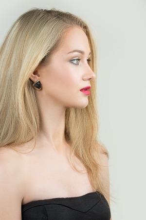 mujer rubia desnuda: hermosa chica con labios rojos y pendientes. Foto de la moda