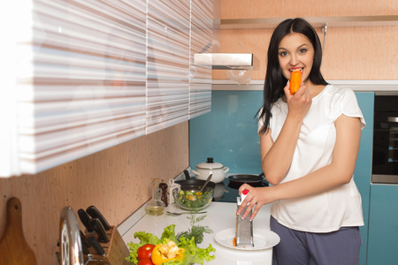 Girl in the kitchen eating a carrot. photo