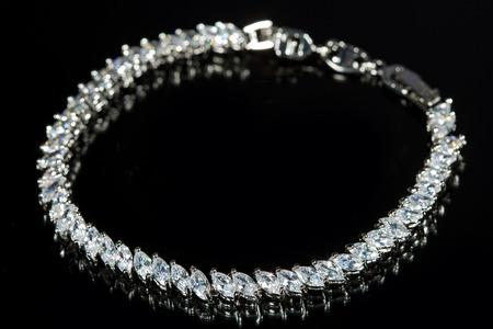silver bracelet with diamonds on black background. photo