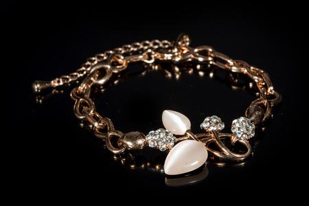 gold bracelet on black background. photo