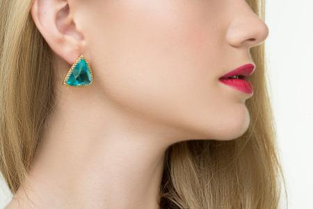 diamond earrings: close up of beautiful woman wearing shiny diamond earrings