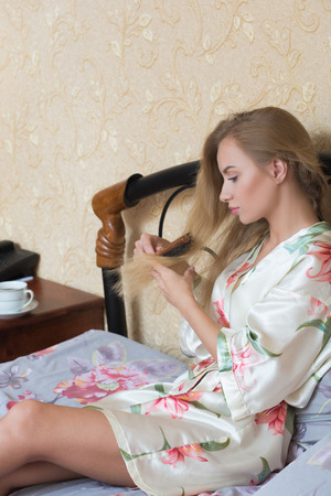 Sexy  Girl Wearing White Nightdress Combing her Hair While Sitting on a Chair at her Room.