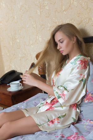 evocative: Sexy  Girl Wearing White Nightdress Combing her Hair While Sitting on a Chair at her Room.