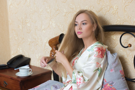 tantalizing: Sexy  Girl Wearing White Nightdress Combing her Hair While Sitting on a Chair at her Room.