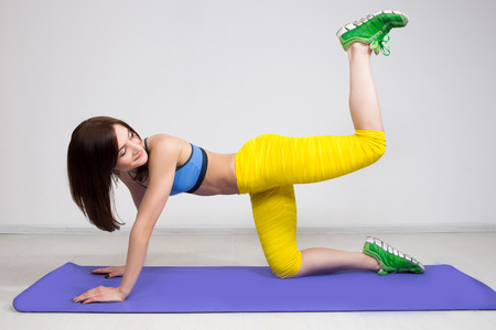 brawny: happy cutie athletic girl ,  execute exercise on muscles belly Stock Photo