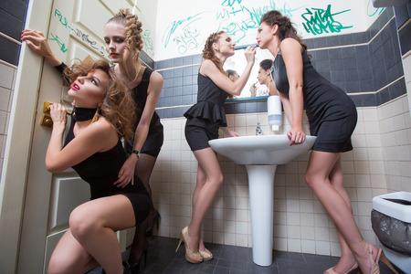borracho: chica borracha en barras de tocador. hermosas mujeres en vestidos de noche en la intoxicación alcohólica Foto de archivo