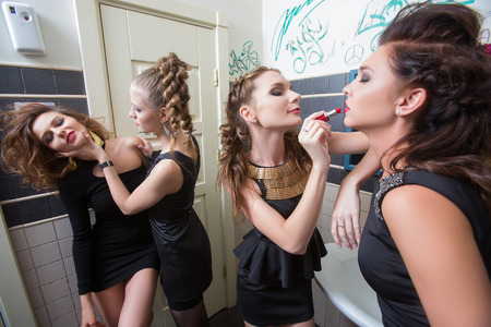 debauch: drunk girl in toilet bars. beautiful women in evening dresses in alcoholic intoxication