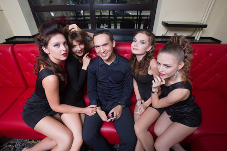 Portrait of sexy lovelace man surrounded by hot women wanting of proposal from him
