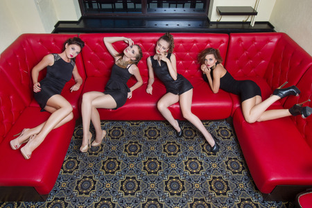 ankles sexy: Four beautiful girl in black short dress on a red couch Stock Photo