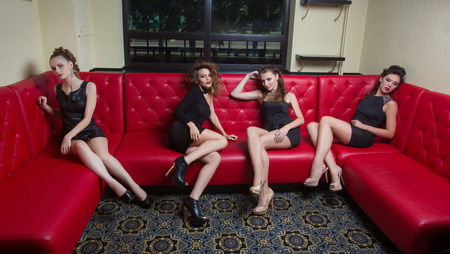 clothing model: Four beautiful girl in black short dress on a red couch Stock Photo
