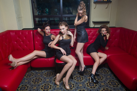 red couch: Four beautiful girl in black short dress on a red couch Stock Photo