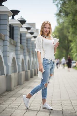 Young stylish woman drinking coffee to go in a city street Zdjęcie Seryjne