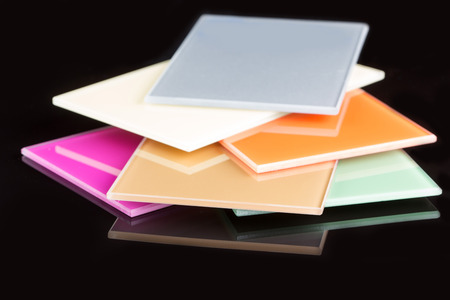 brink: a stack of colored glass on a black background. design, glass sheets Stock Photo