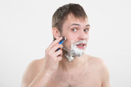 good grooming: Sexy handsome young man with a shaving foam