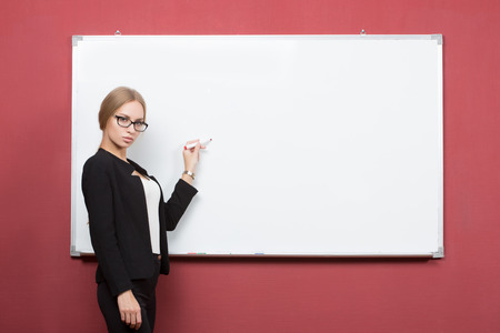 a portrait of business woman pointing at the whiteboard