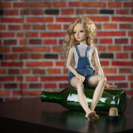 beautiful doll with a bottle. the concept of alcoholism