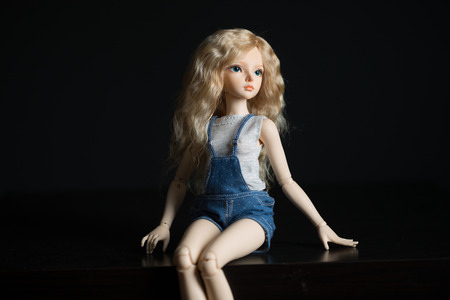 Beautiful doll sits on a light background. Stock Photo