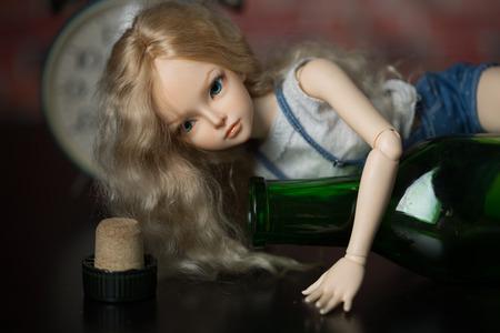 alcoholismo: hermosa mu�eca con una botella. el concepto de alcoholismo
