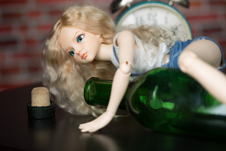 alcoholism: beautiful doll with a bottle. the concept of alcoholism