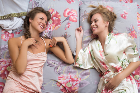 sisters sexy: Portrait of blond sisters or sexy girl friends having fun relaxing in pajamas lying on white bed looking at camera