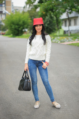 roomy: sexy girl in a red hat with ears, holding a bag on the street Stock Photo