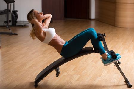 ejercicio aeróbico: Joven y bella mujer en ropa deportiva entrenando sus abdominales. aparatos de entrenamiento