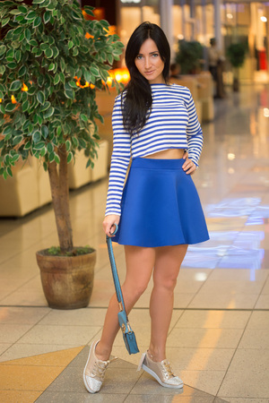 sexual activities: girl in a striped blouse with a bag walks around the store. frock