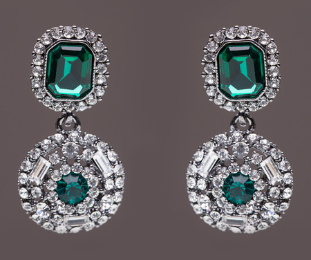 lapis: earrings with green stones on the gray background